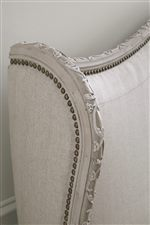 Upholstered Shelter Bed with Nailhead Trim and Intricate Floral Relief Carving