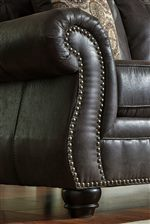 Shaped Rolled Arms with Nailhead Trim. Turned Wood Feet.