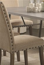 Dining Chairs Add to the Industrial Yet Soft Look with Tan Fabric Upholstery and Oversized Nailhead Studs