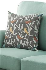 Grey pillow with white branch and blue, yellow, and red bird accents