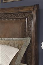 This image highlights both the intricate carving design and upholstered panel headboard bordered by nail head trim.