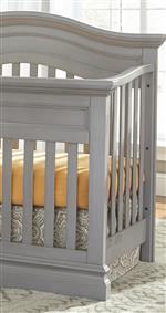 Clean slatted crib with a curved, serpentine top