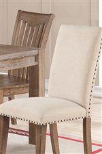 Upholstered Accents in a Vanilla Fabric with Nailhead Trim Provide Contemporary Sophistication