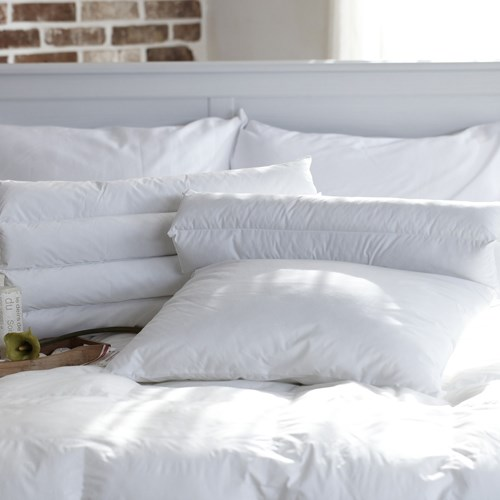 Bed with assortment of pillows on it.