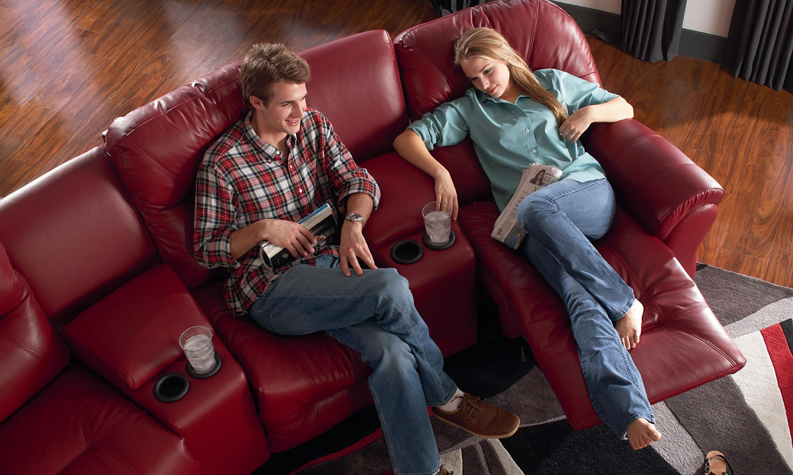 young couple sitting on red leather sectional