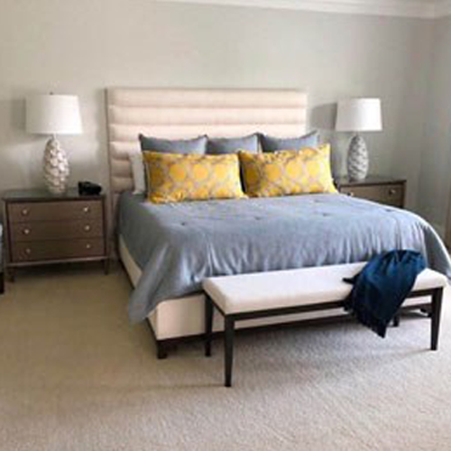white bed with blue sheets and yellow throw pillows