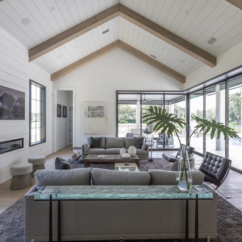 living room with grey sofas and birch ceiling beams