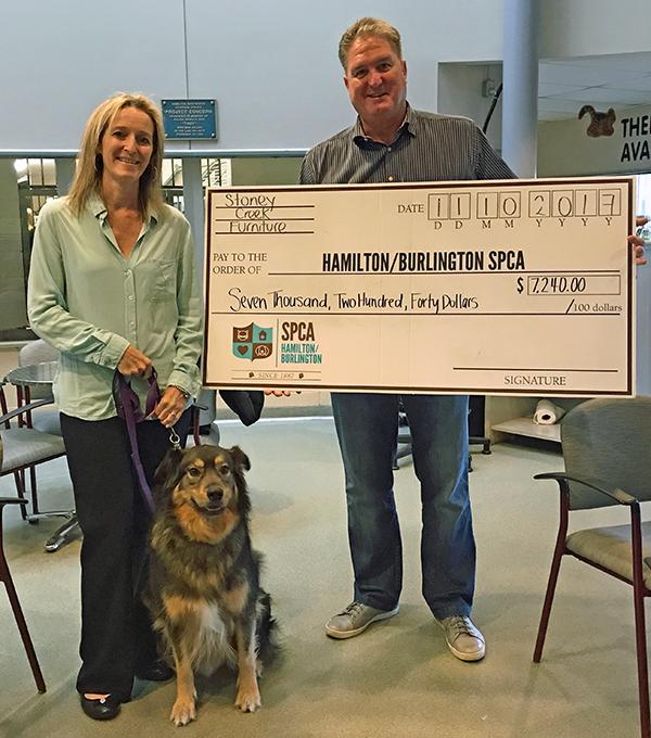 Man woman and dog with a big check