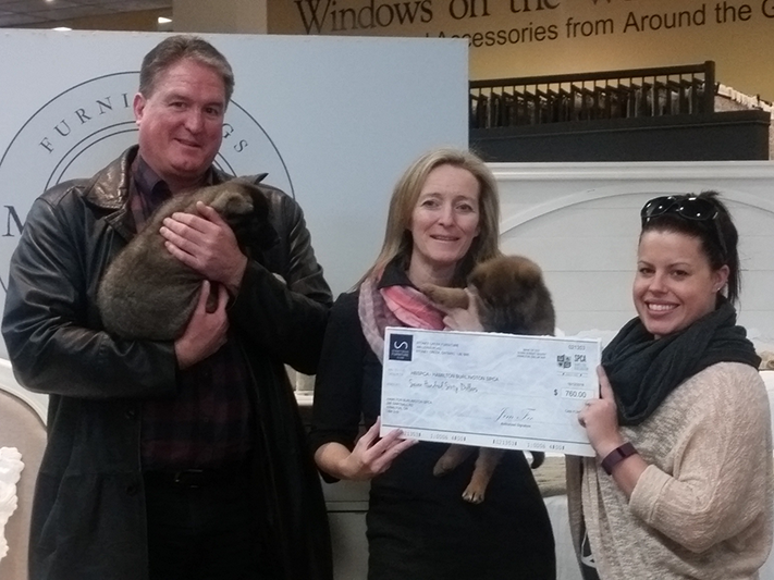 People holding puppies and a check