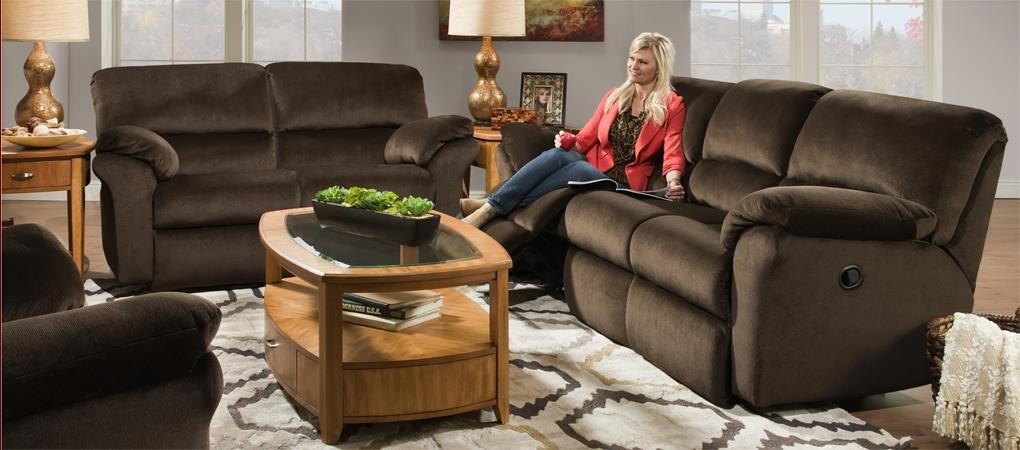 Woman sitting on brown upholstered reclining sofa relaxing.