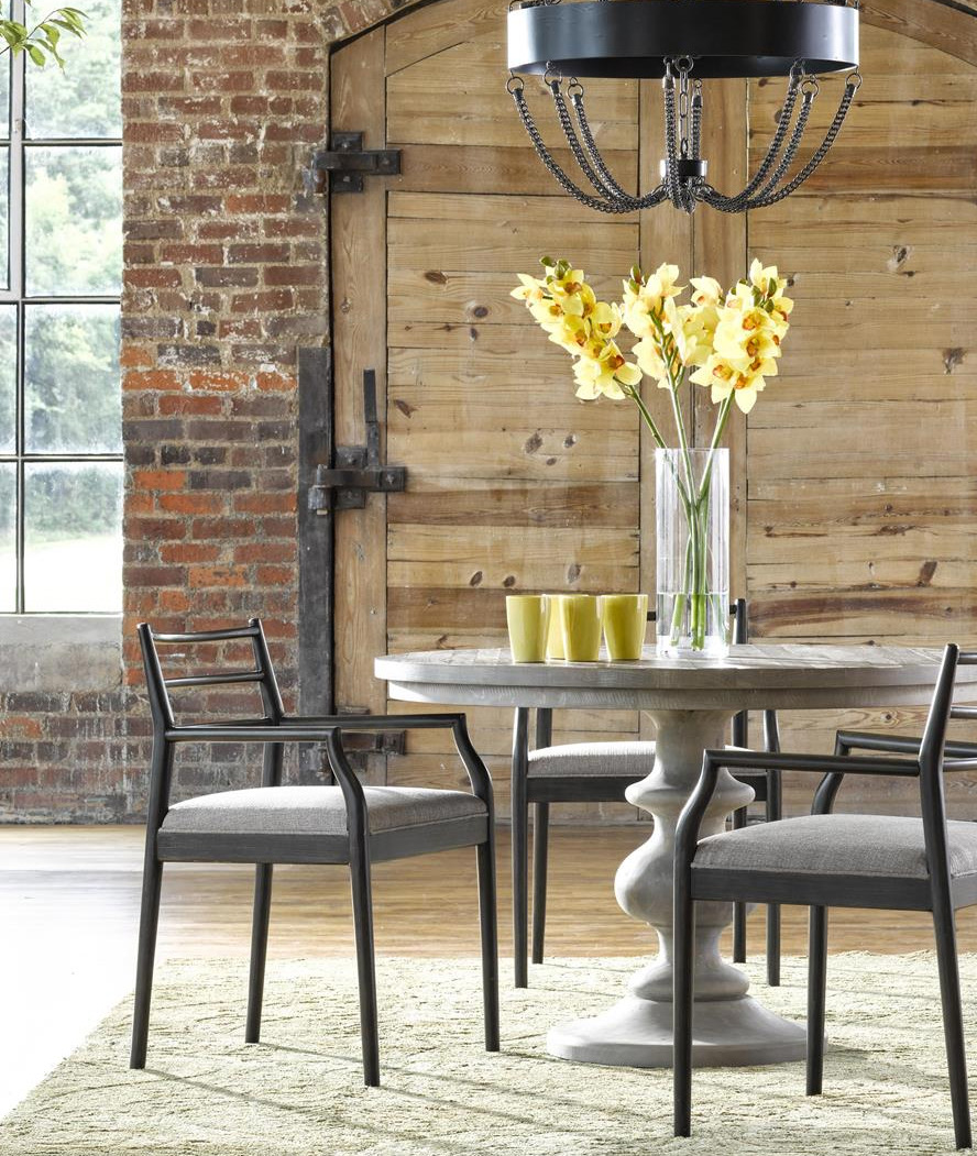 modern dining table with yellow flowers in a vase on top and wooden door in the background