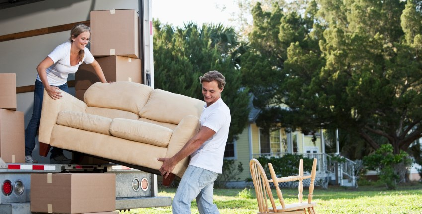 Two people lifting couch out of delivery truck