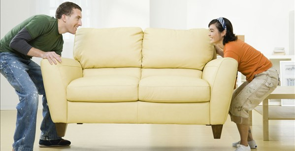 Two people placing couch in living room