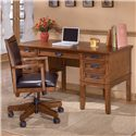 Ashley Furniture Cross Island Mission Office Leg Desk with Storage - Shown with keyboard drawer closed and desk chair