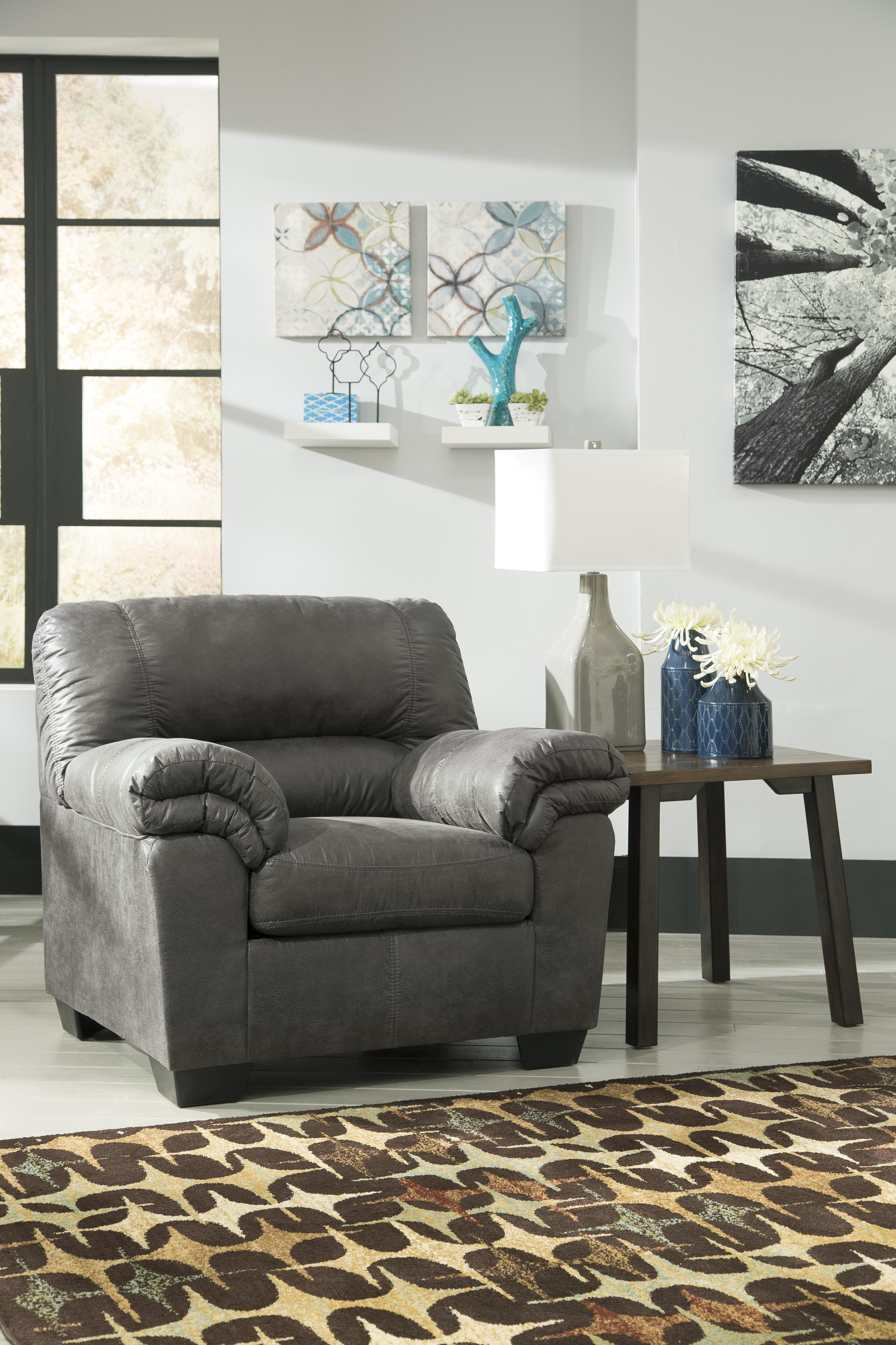 Signature design by ashley bladen casual faux leather chair ottoman royal furniture chair for Faux leather living room furniture